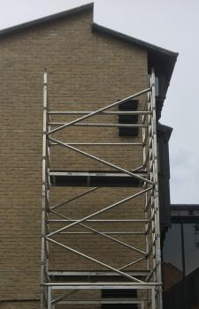 Scaffolding at the end of the Sainsbury Building allows us to put up some of the new swift boxes .